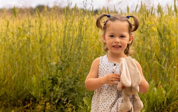 Petite fille mignonne avec un lièvre en peluche dans une robe légère 1-3 dans le domaine des épillets de seigle en été