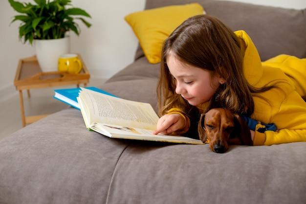 La petite fille mignonne lit un livre allongé sur le lit avec une éducation à domicile de teckel nain