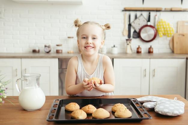 Petite fille mignonne mangeant des biscuits fraîchement cuits au four dans la cuisine. famille heureuse. tonifiant.