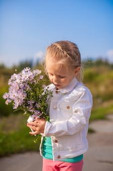 Petite fille mignonne marchant avec un bouquet de fleurs