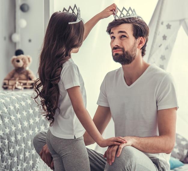 La petite fille mignonne met une couronne sur son jeune papa.
