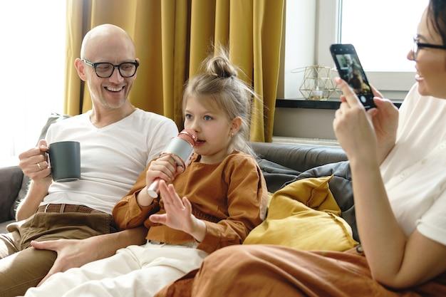 Petite fille mignonne avec un microphone de karaoké chantant pour ses parents à la maison