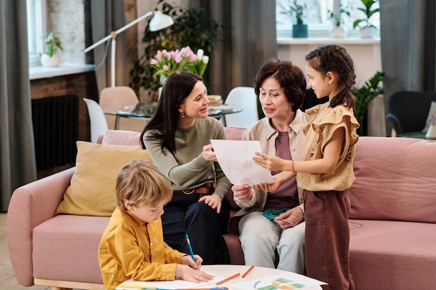 Petite fille mignonne montrant son dessin à la mère et à la grand-mère