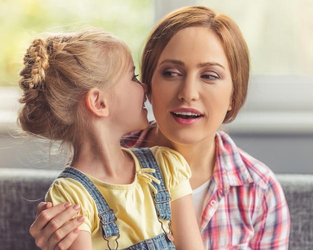 La petite fille mignonne murmure quelque chose dans sa mère.