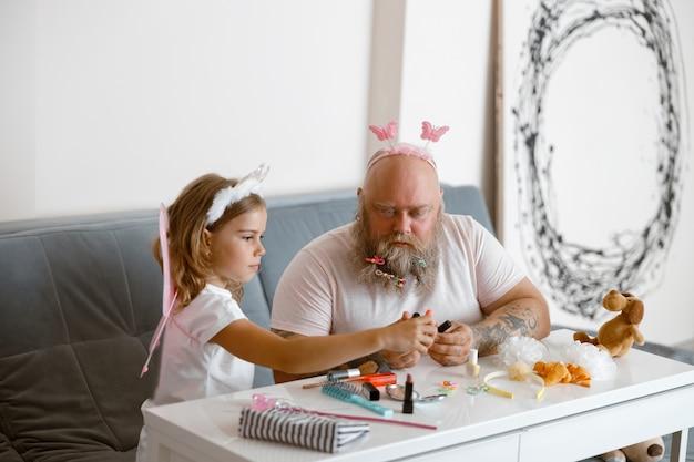 La petite fille mignonne avec le papa barbu choisit le vernis à ongles dans le salon contemporain