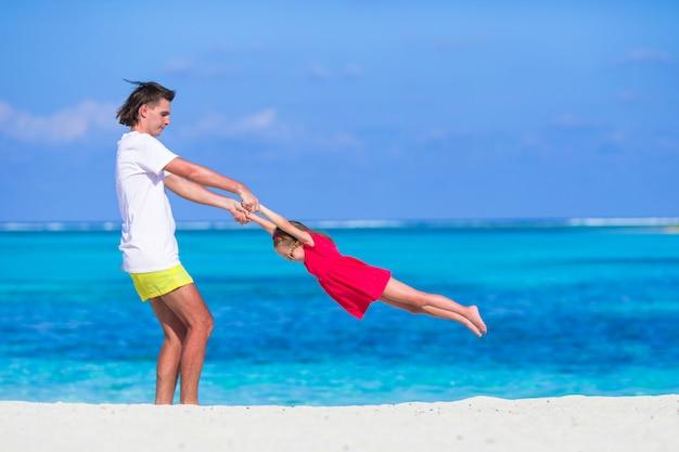 Petite fille mignonne et papa pendant les vacances à la plage tropicale