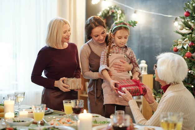 Petite fille mignonne passant coffret cadeau avec cadeau de noël à son arrière-grand-mère lors de la fête de famille à la maison