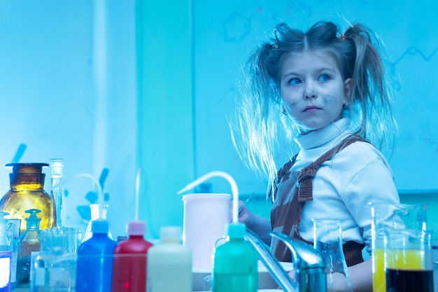 Petite fille mignonne pendant le cours de chimie à l'école