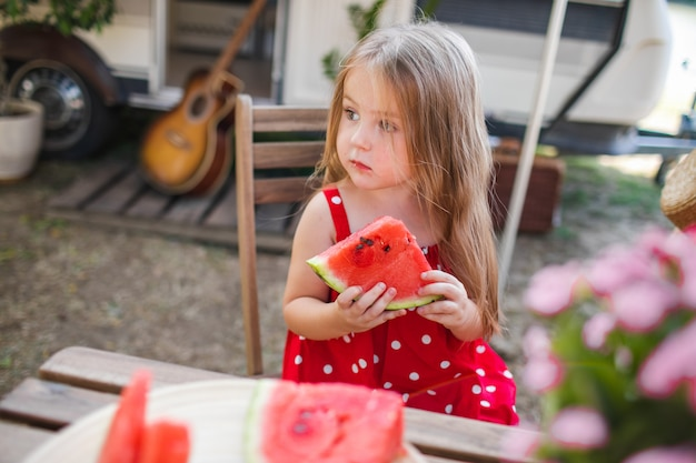Petite fille mignonne sur un pique-nique avec la pastèque