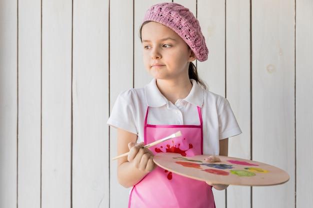 Une petite fille mignonne portant chapeau rose tissé tenant un pinceau et une palette de peinture