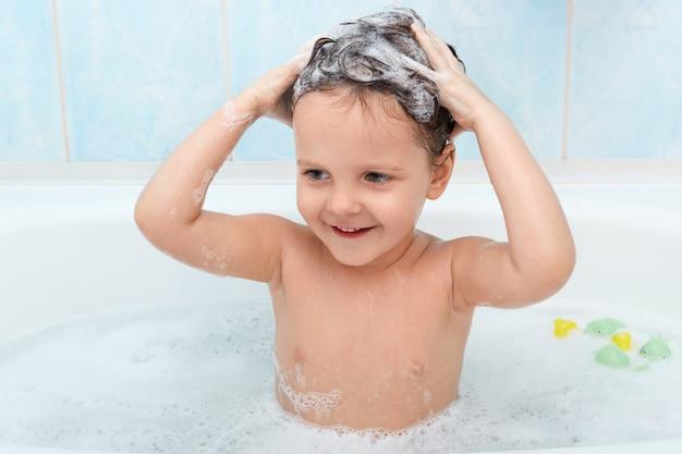 Petite fille mignonne prenant un bain, se lavant les cheveux avec du shampoing