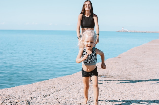 Petite fille mignonne qui court de maman en forme sur la plage