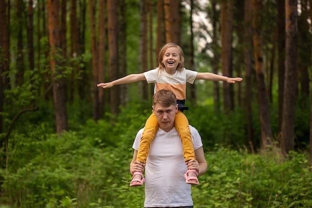 Petite fille mignonne de race blanche assise sur les épaules de son père dans la forêt