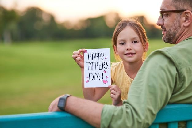 Petite fille mignonne regardant la caméra et montrant la fête des pères heureuse de carte postale à la main tout en dépensant