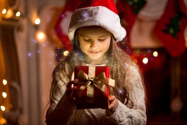 Petite fille mignonne regardant à l'intérieur de la boîte de cadeau de noël rougeoyante
