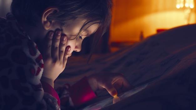 Petite fille mignonne regardant la tablette
