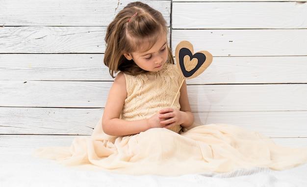 Petite fille mignonne en robe assise sur fond en bois blanc avec un coeur dans ses mains, concept de vacances