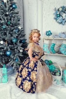 Petite fille mignonne en robe de princesse près de l'arbre du nouvel an, beau décor de noël