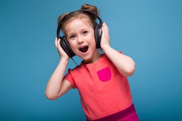 Petite fille mignonne en robe rose et des écouteurs