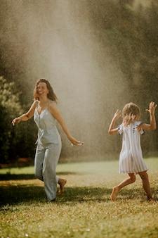 Petite fille mignonne s'amusant avec de l'eau sous l'arroseur d'irrigation avec sa mère