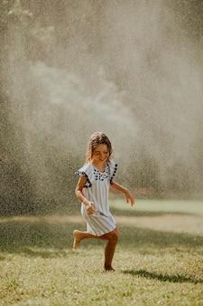 Petite fille mignonne s'amusant avec de l'eau sous l'arroseur d'irrigation