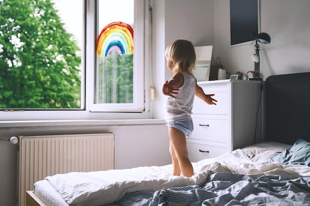 Petite fille mignonne s'amusant à sauter sur le lit sur fond de fenêtre avec un arc-en-ciel peint
