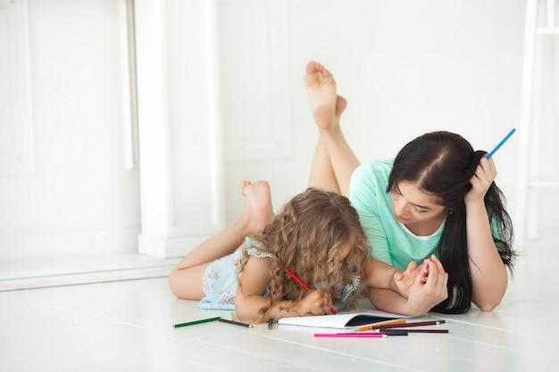 Petite fille mignonne et sa mère dessinant avec des crayons colorés et s'amusant ensemble. joli enfant et maman jouant à l'intérieur. famille heureuse, passer du temps en dessinant.