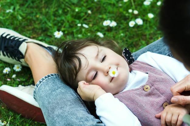 Une petite fille mignonne avec sa mère est allongée dans un champ de camomille