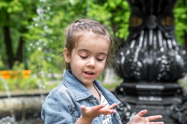 Petite fille mignonne se mouille les mains dans la fontaine