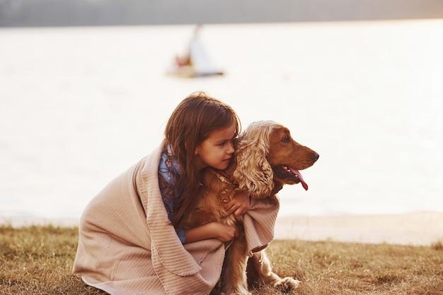 Une petite fille mignonne se promène avec son chien à l'extérieur par beau temps