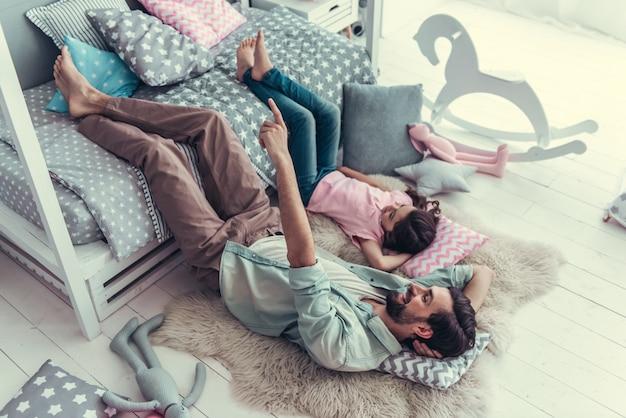 La petite fille mignonne et son papa sont couchés sur le sol.