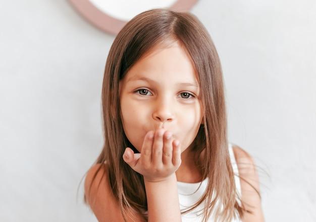 Petite fille mignonne soufflant un baiser aérien droit dans la caméra
