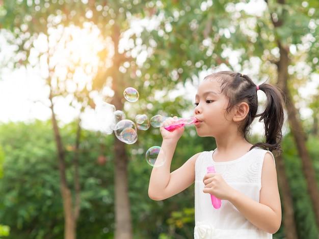 Petite fille mignonne soufflant des bulles dans le jardin.