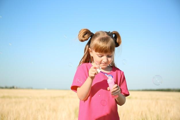 Petite fille mignonne soufflant des bulles de savon dans le domaine le jour ensoleillé