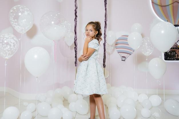 Une petite fille mignonne sourit et pose dans le contexte d'une balançoire avec des ballons.