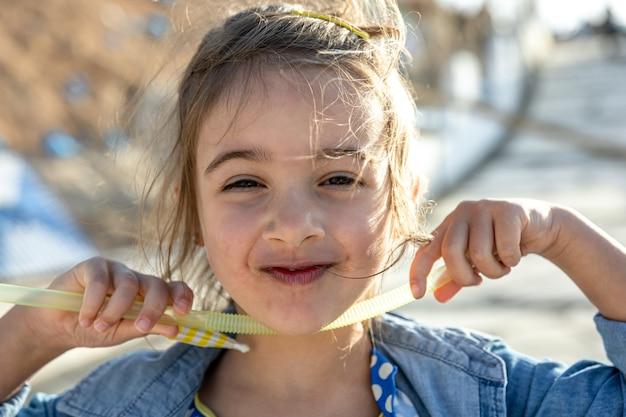 Une petite fille mignonne sourit et regarde la caméra.
