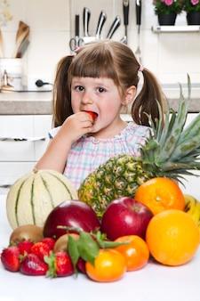 Petite fille mignonne tenant et mangeant une fraise dans la cuisine
