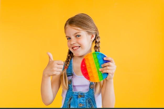 Petite fille mignonne tenant pop it jouet antistress sur fond jaune, isoler. espace de copie