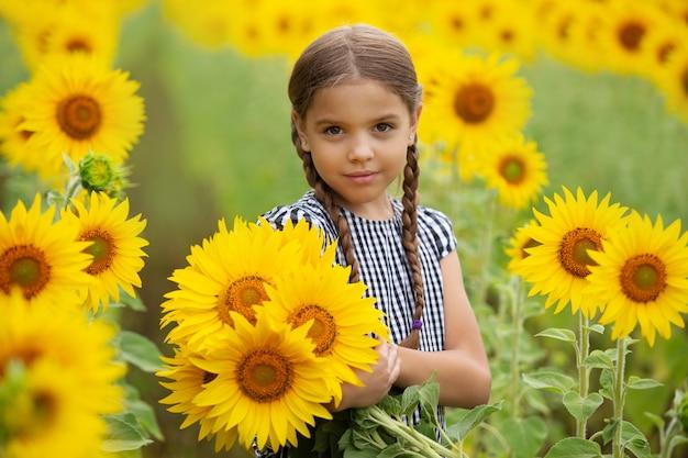 Petite fille mignonne tenant des tournesols