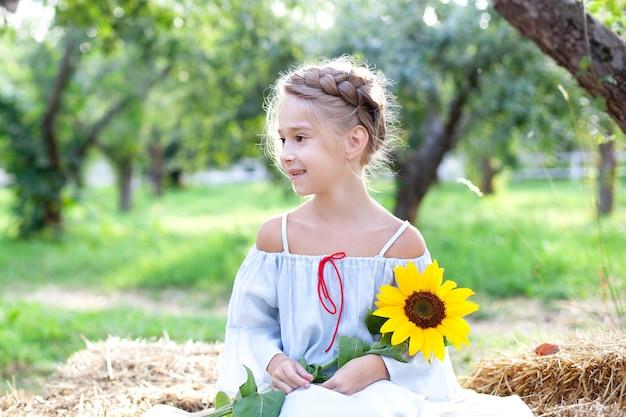 La petite fille mignonne tient un enfant de tournesol avec un tournesol dans l'été de jardin