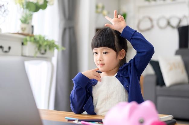 Une petite fille mignonne utilise un ordinateur portable pour étudier en ligne via internet à la maison. concept d'apprentissage en ligne pendant la période de quarantaine.