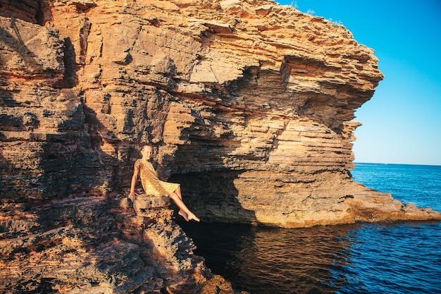 Petite fille mignonne en vacances sur les rochers à la mer