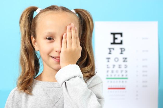 La petite fille mignonne vérifie la vue avec un essai de vue d'ophtalmologiste