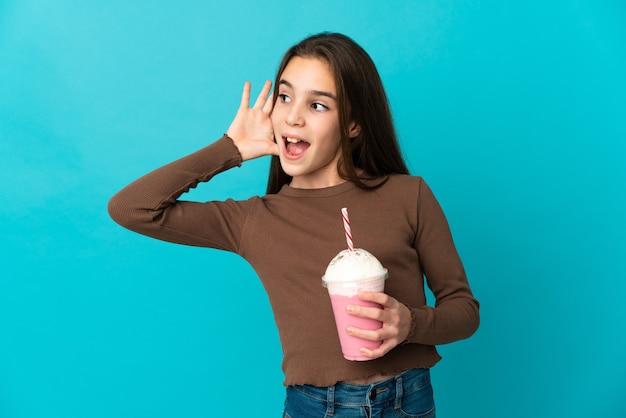 Petite fille avec milk-shake aux fraises isolé sur fond bleu en écoutant quelque chose en mettant la main sur l'oreille