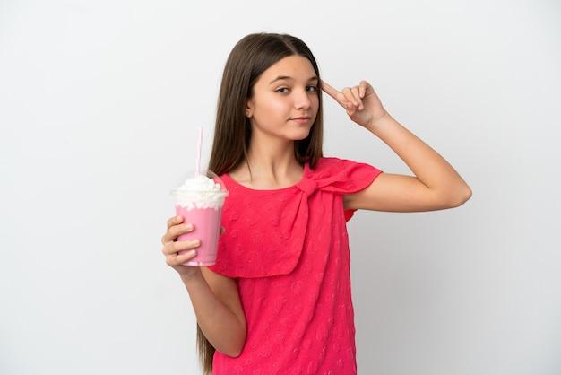 Petite fille avec milkshake aux fraises sur fond blanc isolé ayant des doutes et de la pensée