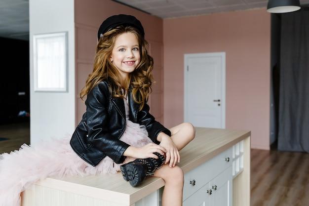 Petite fille à la mode dans une robe rose et une veste en cuir noir