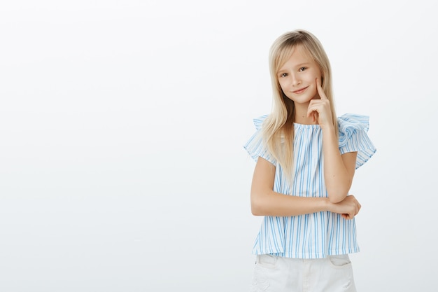Petite fille à la mode sait tout sur les robes mignonnes. heureux enfant émotive heureux aux cheveux blonds, tenant le doigt sur la joue et souriant largement, ayant une bonne idée à l'esprit sur un mur gris