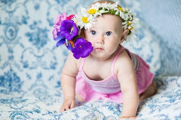 Petite fille d'un mois sur le lit en regardant la caméra