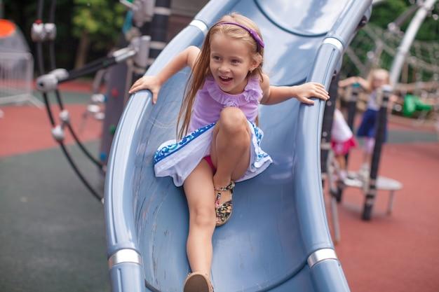 Petite fille monte sur la colline dans un parc d'attractions