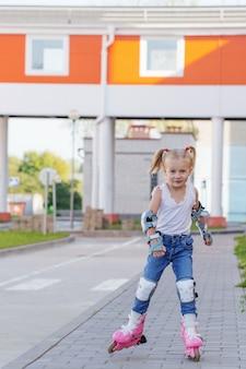 Petite fille monte des patins à roues alignées